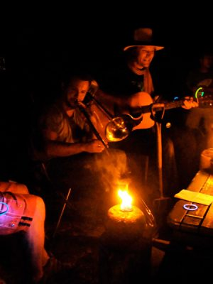 Photograph of musicians playing around fire